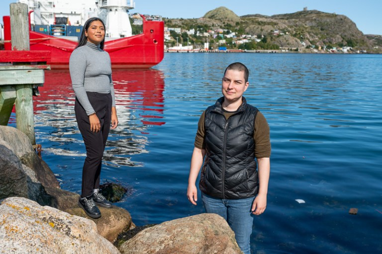 Nadia Duman (left) and Max Liboiron stand on rocks by the shore of the Atlantic Ocean in St. John's.