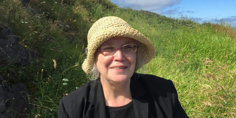 A smiling woman in a straw hat, glasses and a black top sits on the grass