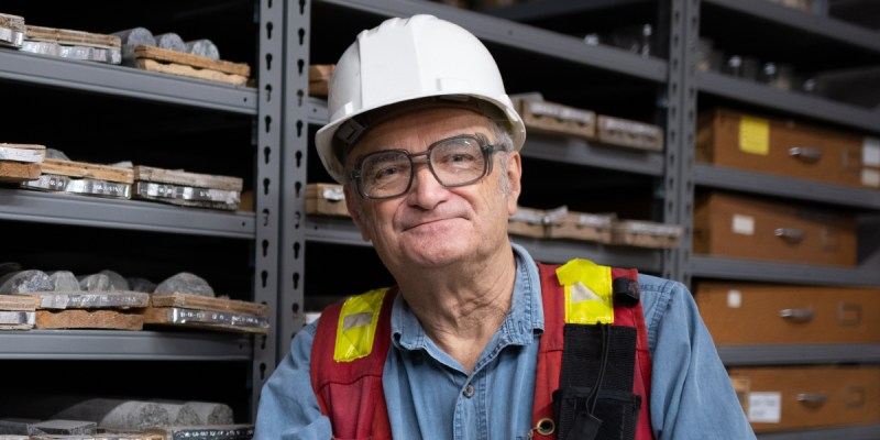 A man in PPE stands in front of racks of rock samples