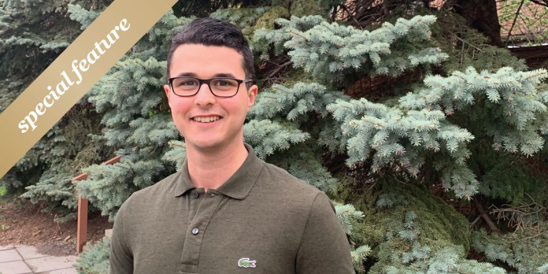 """A man with dark hair and glasses and green shirt stands in front of trees. A gold sash with the words """"special feature"""" is in the upper left-hand corner."""