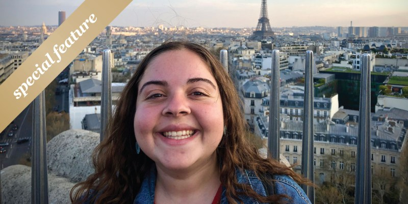 A woman takes a selfie with Paris in the background