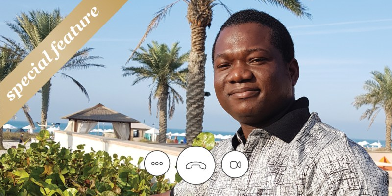 """A man stands in front of a beach with palm trees. Telephone and computer icons are at the bottom. A gold sash with """"special feature"""" on it is in the upper left-hand corner."""