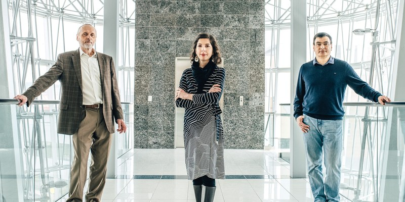 Two men and a woman stand six feet apart in a building lobby with windows behind them.