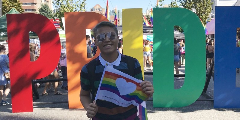 Nel Jayson Santos, wearing a polo shirt and shorts, holds a Pride flag and stands in front of large letters spelling Pride.