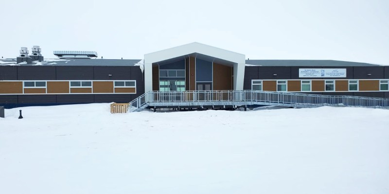The Cambridge Bay Campus of Nunavut Arctic College is pictured, a long, one-storey building with a center peak and yellow-brown siding. It is surrounded by snow.
