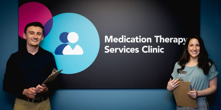 Pharmacists stand by the sign for the Medication Therapy Services (MTS) Clinic