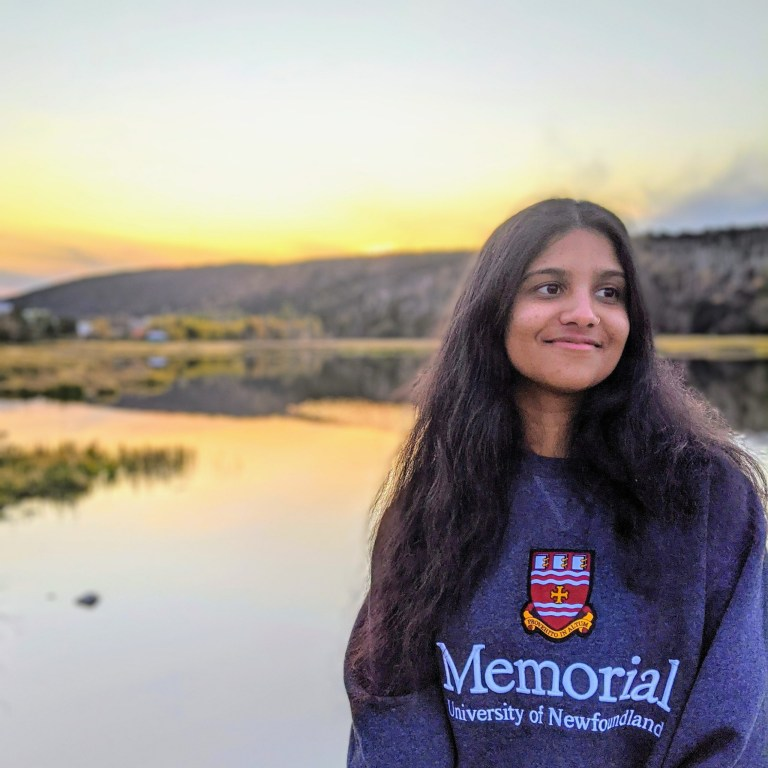 A woman with long brown hair wearing a blue Memorial sweatshirt stands in front of a pond at sunset