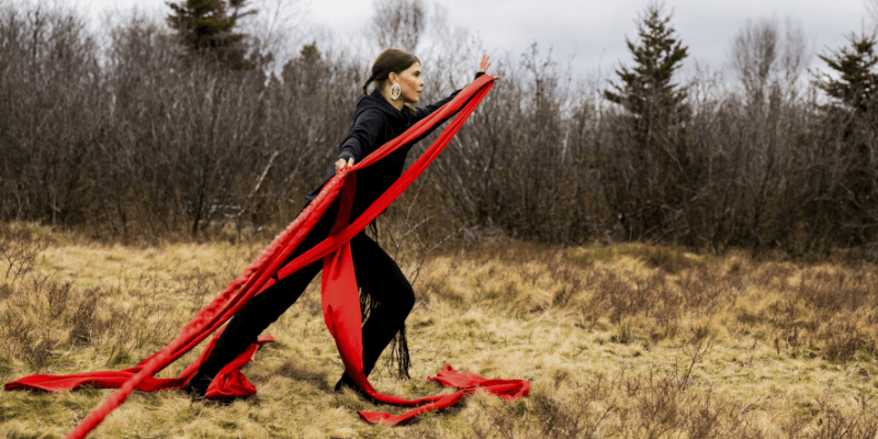 A woman dressed in black moves with a very long piece of silky red material in a woods setting.