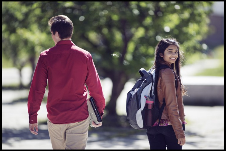 Two students walking outside, with one looking back at the camera.