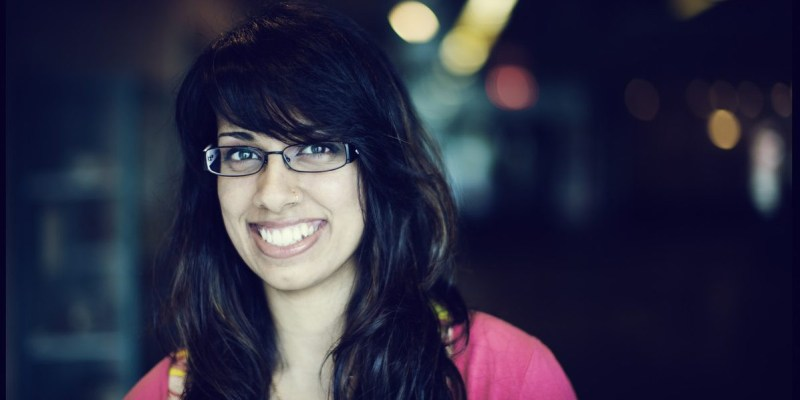 Undergraduate student wearing glasses and smiling at the camera