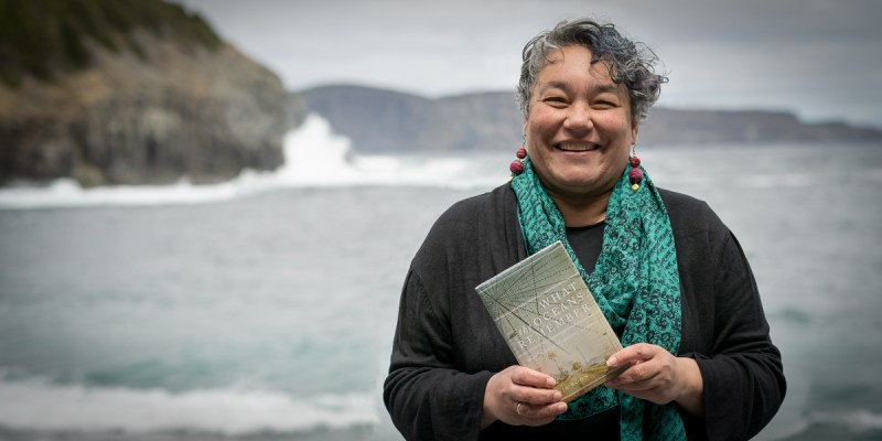 A woman in a black shirt and green scarf with black and grey wavy hair holds a book and stands in front of the ocean.