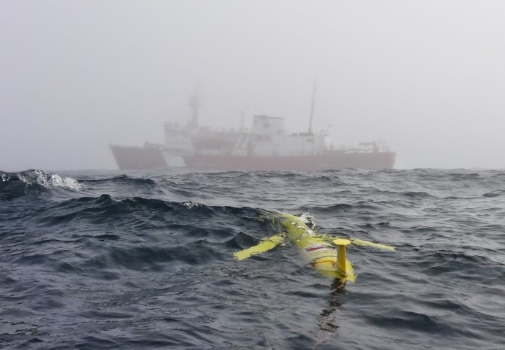 A yellow underwater autonomous vehicle is in the foreground in the ocean, a large red and white vessel is in the background.