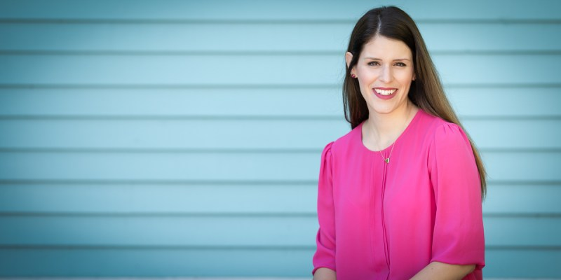 Dr. Gillian Morrissey wears a bright pink top and is seated against a teal background.