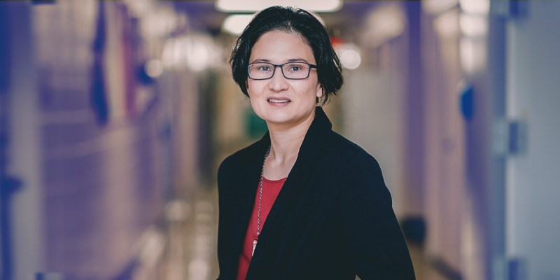 Dr. Sherri Christian, an associate professor in the Department of Biochemistry, Faculty of Science, who is also cross-appointed with the Faculty of Medicine is wearing a black suit jacket with a red shirt and smiling.