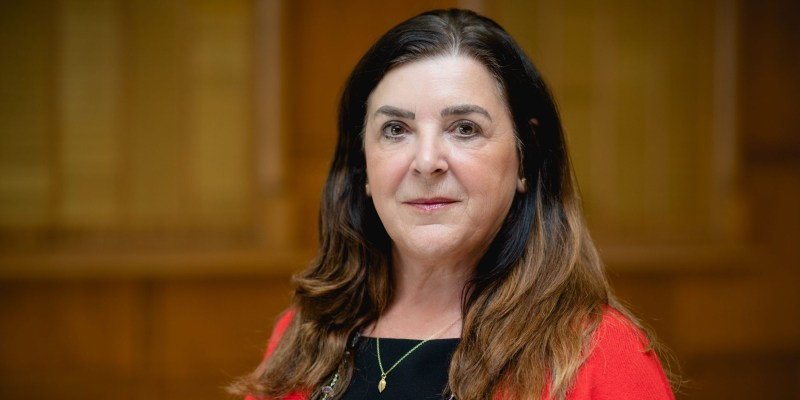 Vianne Timmons looks at the camera without smiling, wearing a red cardigan, black shirt and silver chain.