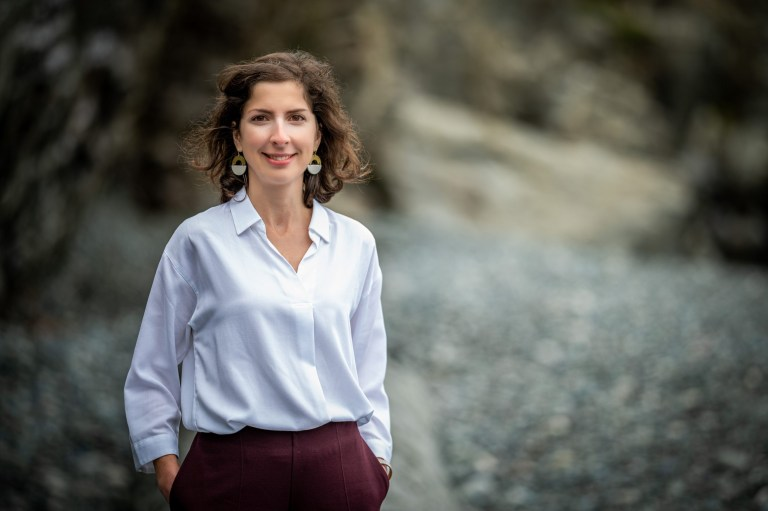 Smiling with hands in pocket, Dr. Paula Mendonça wears a white top.