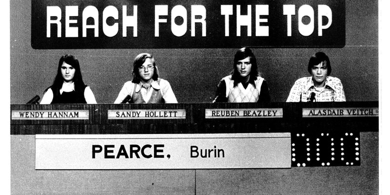 """A black and white picture of four young people sitting as a panel with their names on signs beneath. A large sign saying """"Reach for the Top"""" is on the wall behind them."""