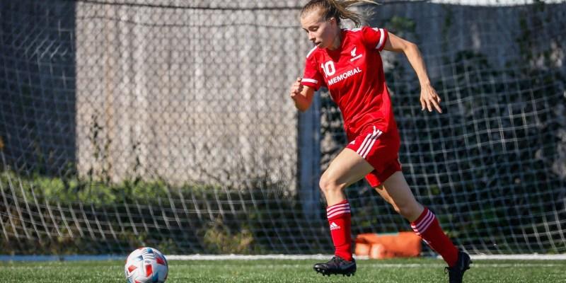 Katie Joyce is wearing a red Sea-Hawks uniform and kicking a soccer ball