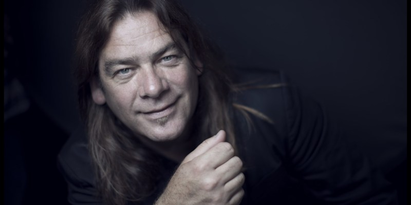 Alan Doyle is wearing a black jacket and smiling