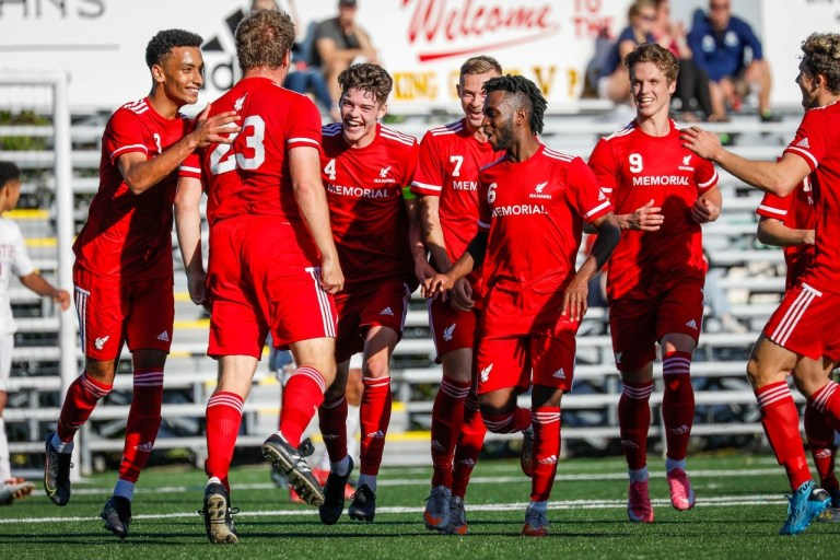 Seven Sea-Hawks wearing red uniforms are smiling