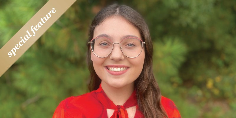 """Emma Butler wears red glasses and a red shirt and stands in front of trees. A gold sash with the words """"special feature"""" in white text appears in the upper right-hand corner."""