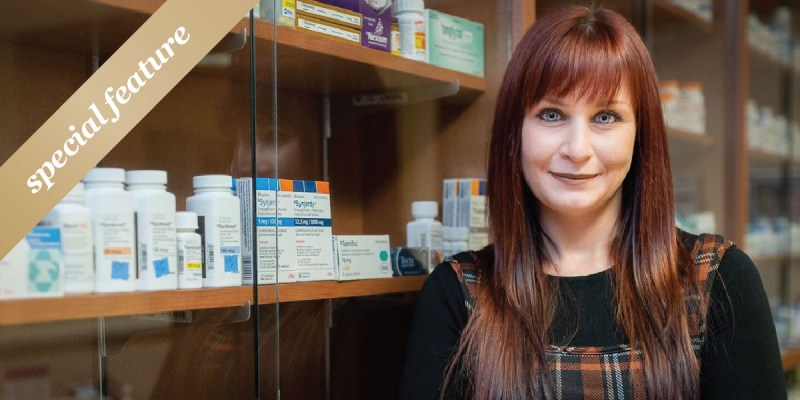 """Jessica Biggin wears a black shirt and tartan dress and stands in front of a cabinet of prescription medications. A gold sash with the words """"special feature"""" in white text appears in the upper left-hand corner."""