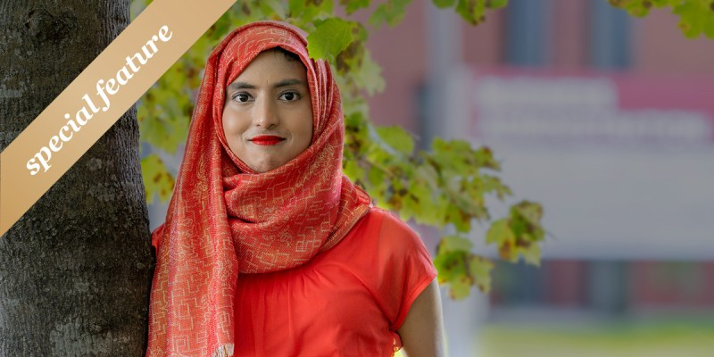 """Jannatul Alam leans against a tree and wears a red head covering and shirt. Leaves and a building are blurred out in the background. The words """"special feature"""" appear in white on a gold sash in the upper left-hand corner."""