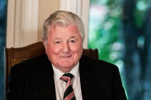 Noel Browne wears a black blazer, white shirt and a pink, white and green tie. A window with trees showing is in the background.