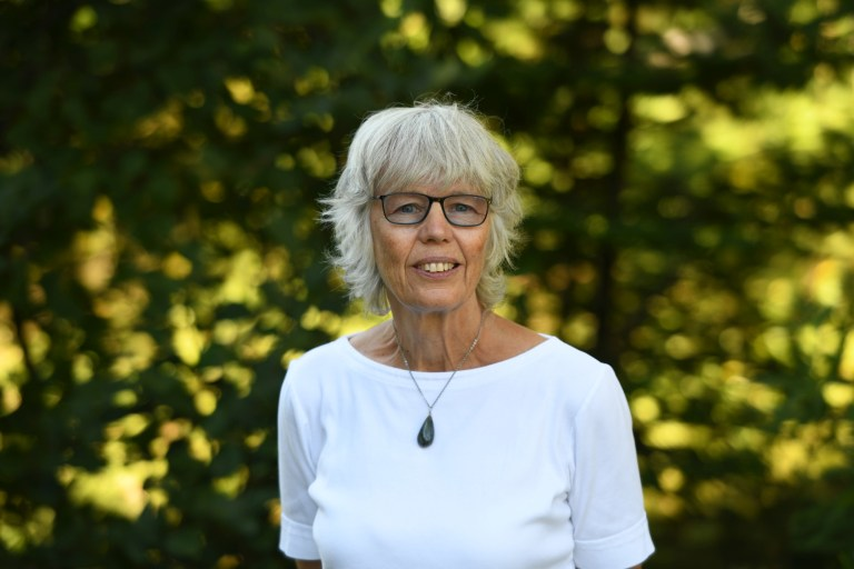 Dr. Uta Passow wears a white shirt, necklace and dark rimmed glasses.