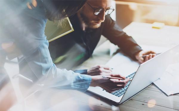 Mujer ayuda a un hombre a registrar la marca de su empresa por internet.