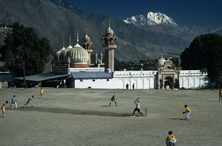 Youth playing a cricket match outside Shahi Mosque, the iconic mosque in Chitral with Tirich Mir in the background