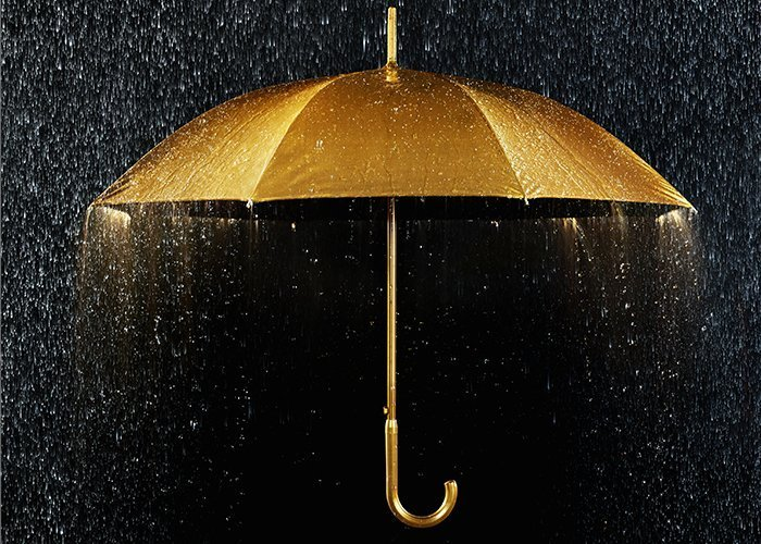A golden umbrella with rain falling on it.