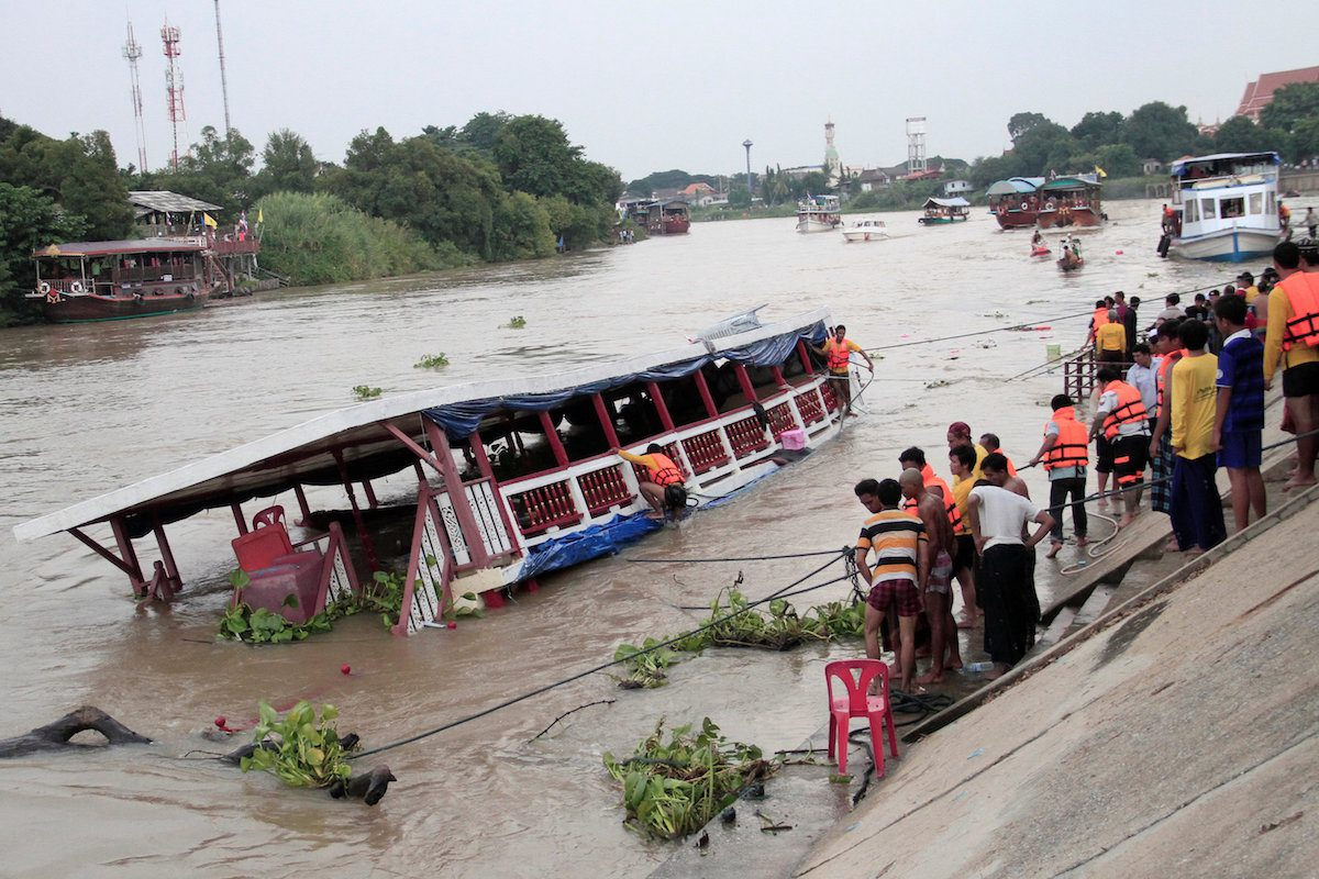 People stand near a boat which according to officials, capsized on the Chao Phraya river while carrying 150 Thai Muslims, in the ancient tourist city of Ayutthaya, Thailand September 18, 2016.  Dailynews/via REUTERS ATTENTION EDITORS - THIS IMAGE WAS PROVIDED BY A THIRD PARTY. EDITORIAL USE ONLY. NO RESALES. NO ARCHIVE. THAILAND OUT.