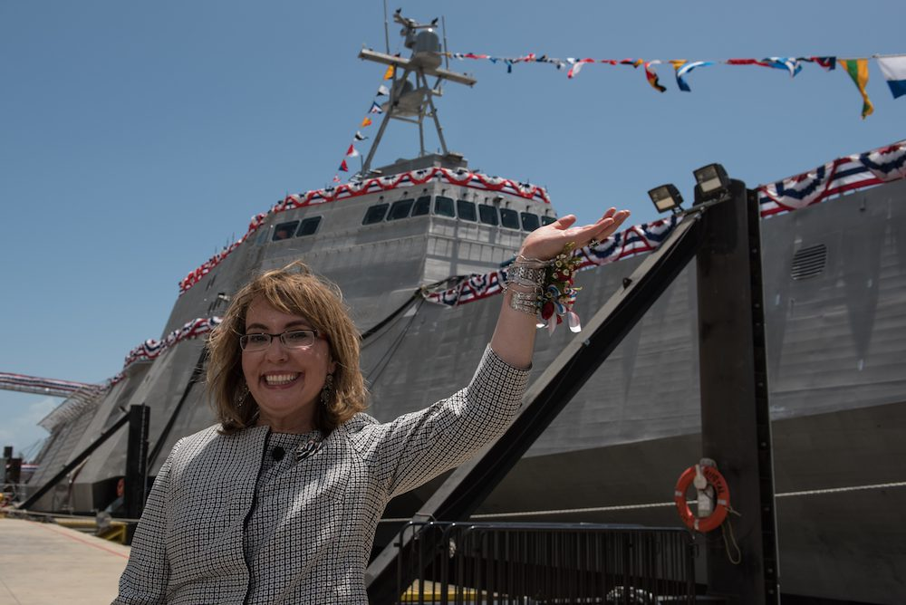 "150613-O-ZZ999-603 MOBILE, Ala. (June 13, 2015) Former U.S. Rep. Gabrielle ""Gabby"" Giffords waves to a crowd in front of the littoral combat ship, USS Gabrielle Giffords (LCS 10), named for her. Giffords was on the stage as Dr. Jill Biden christened the ship at Austal USA in Mobile, Ala. The 419-foot ship was built at the Austal shipyard and is the Navy's 10th littoral combat ship designed to operate in shallow waters near the coast. It is 16th U.S. naval ship to be named for a woman and only the 13th since 1850 to be named for a living person. (Photo courtesy Austal USA/Released)"