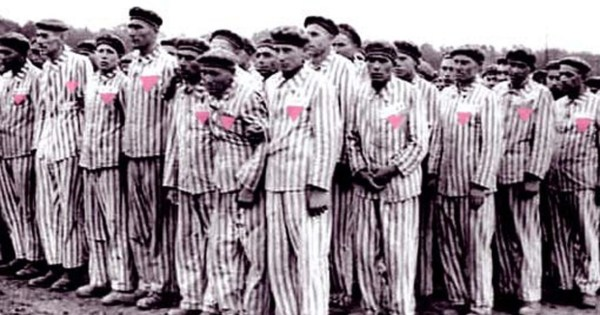 Men queuing in concentration camp wearing the pink triangle
