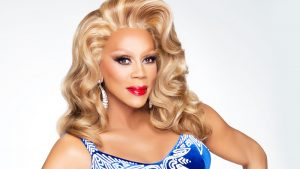 RuPaul smiling with blonde hair, blue dress and red lips