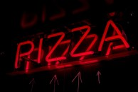 Glowing red pizza sign in Aperitif