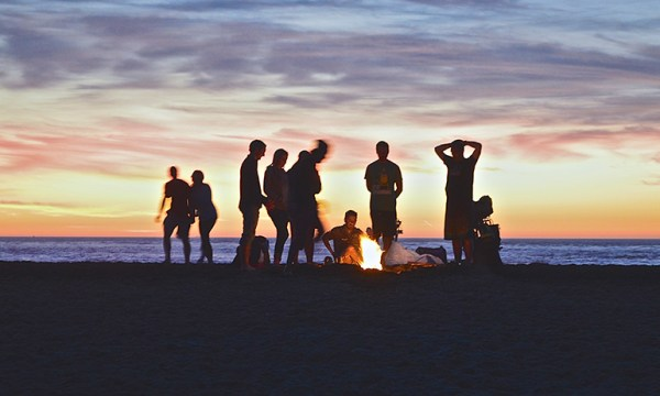 Friends gathered around a fire on a beach at sunset, showing that people is one of the 5 things that get better for young LGBT people