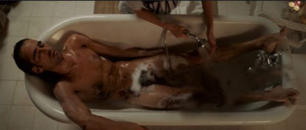 Colin Farrell lying naked in a bath with suds not hiding his full-frontal nudity