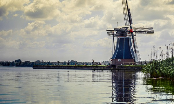 A windmill near a body of water in the Netherlands, which is one of the countries the lgbt Irish diaspora might relocate to