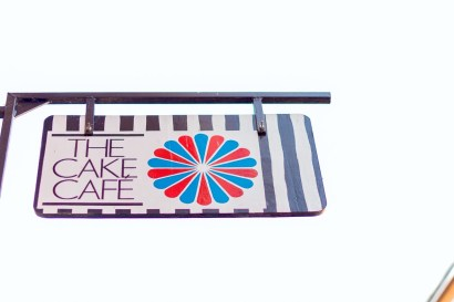 The Cake Cafe sign with a blue and red circle at the cake cafe and slice which are both owned by Ray O'Neill