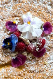 Gorgeous flowers and fruit atop an iced baked good at the cake cafe and slice which are both owned by Ray O'Neill