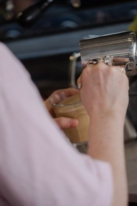A barista making coffee in Two Boys Brew café