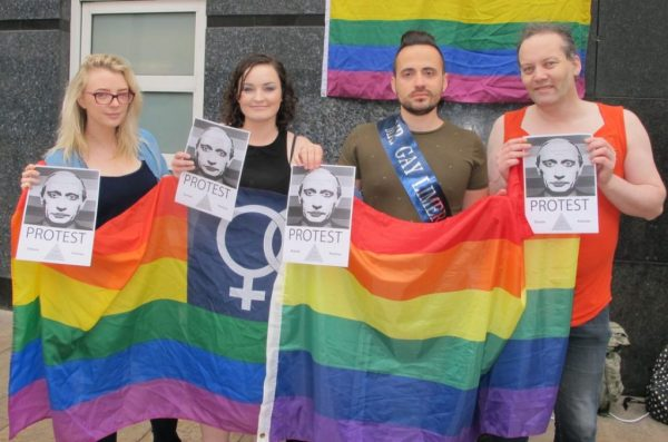 Dr Christian Moretti who is the current Mr Gay Limerick holding a big rainbow flag with other people who will be at Mr & Ms Gay Limerick event by Limerick Pride