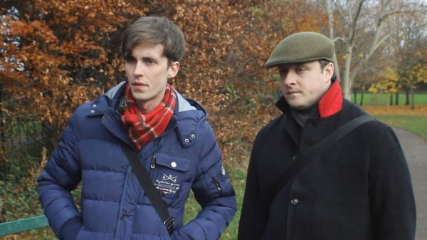 Maurice and Kenny from Awful Gays standing in a park with trees in the background in coats