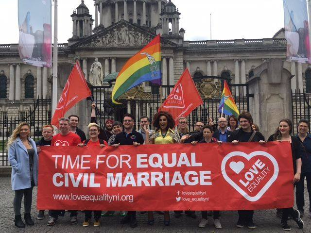 people holding rainbow flags and a sign saying 'time for equal civil marriage'