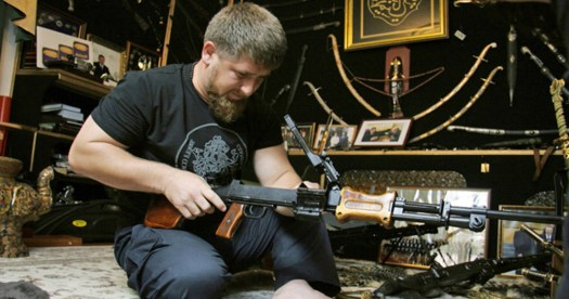 a bearded man assembles a rifle while sitting on a floor