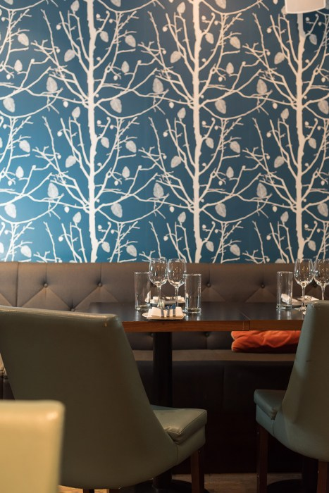 Detail of table and bench at BANG restaurant, behind them a blue and white wallpaper