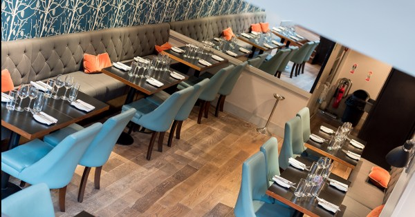 Panoramic image of tables and blue chairs at BANG restaurant