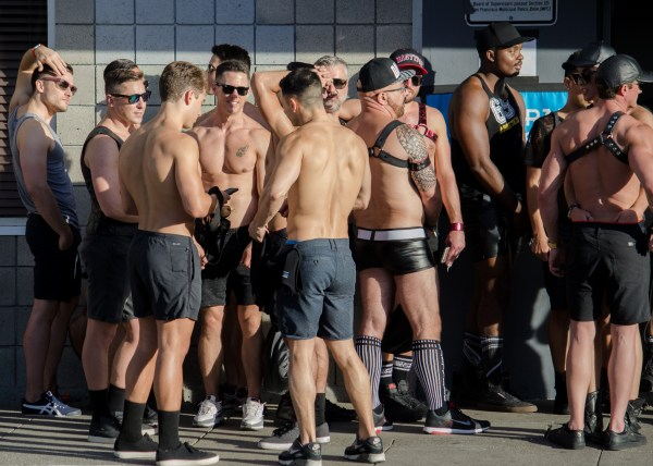 A group of shirtless guys in shorts talking at Folsom street fair.